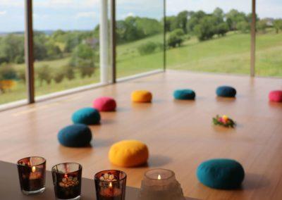 Des coussins de yoga dans la salle Reliance sous un doux rayon de soleil avec vue sur la vallée - Terre et source