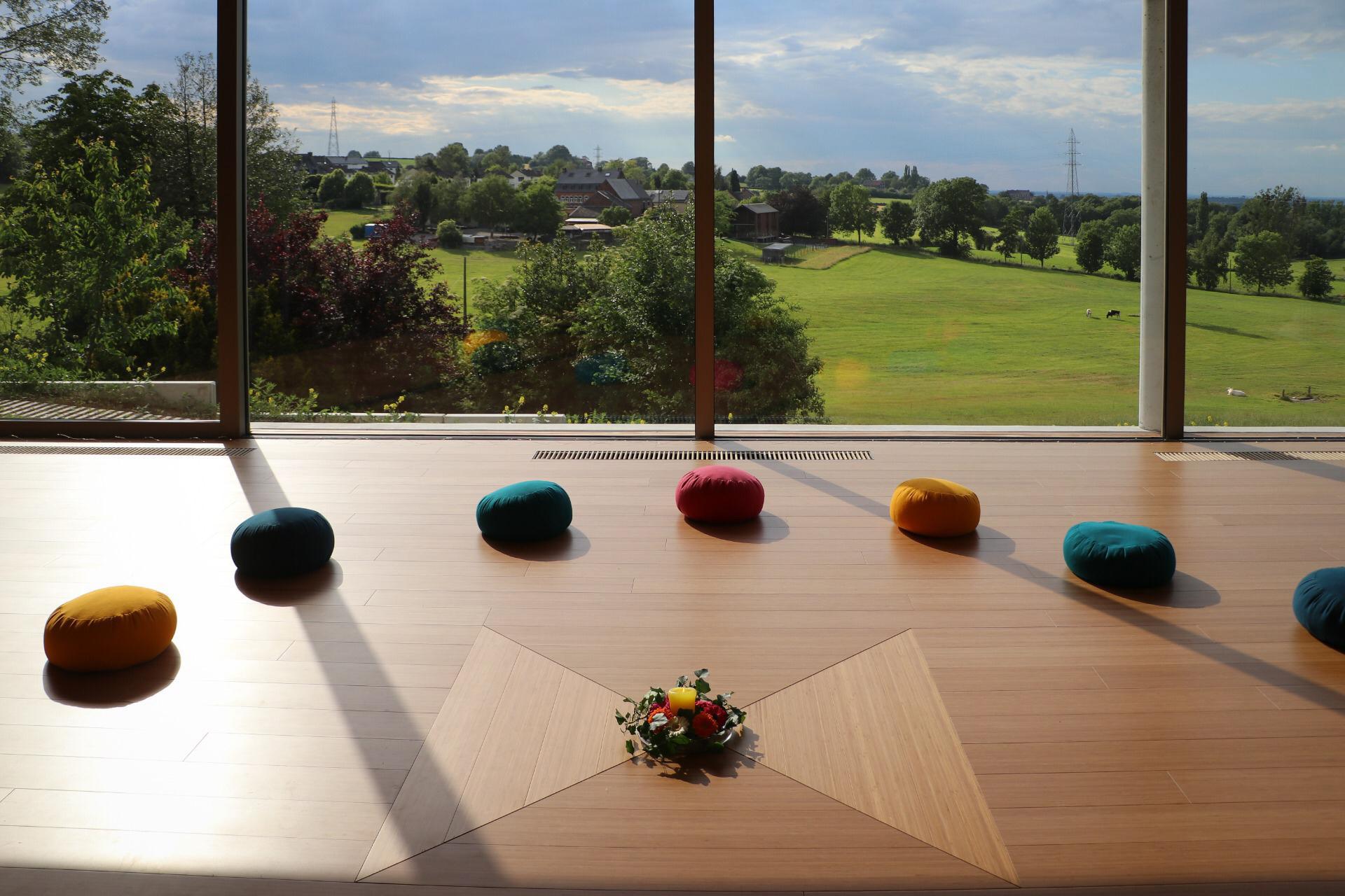 Des coussins de yoga dans la salle Reliance sous un doux rayon de soleil avec vue sur la vallée